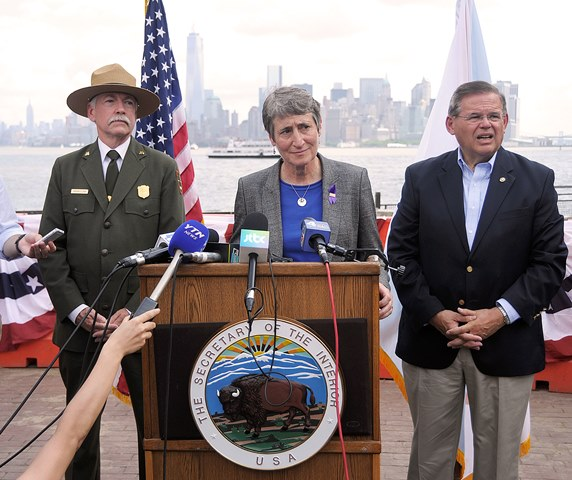 At the reopening of Liberty Island on July 4, 2013, Interior Secretary Sally Jewell listens to a question. National Park Service Director Jon Jarvis and U.S. Senator Robert Menendez stand to either side.