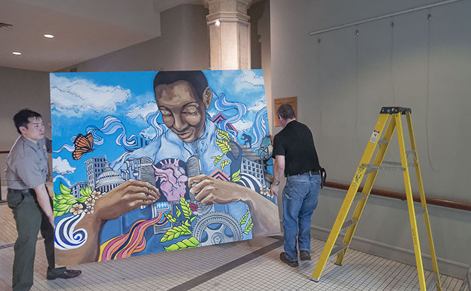NPS Ranger Peter Wong and NPS Museum Technician Brent Talbot work to install one of the six Groundswell murals for a special exhibition at Ellis Island.