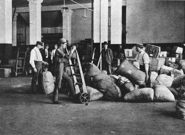 Historic image showing baggage handlers moving cargo in the Baggage Room.