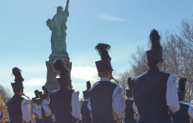 Visiting marching band performing behind the Statue of Liberty.