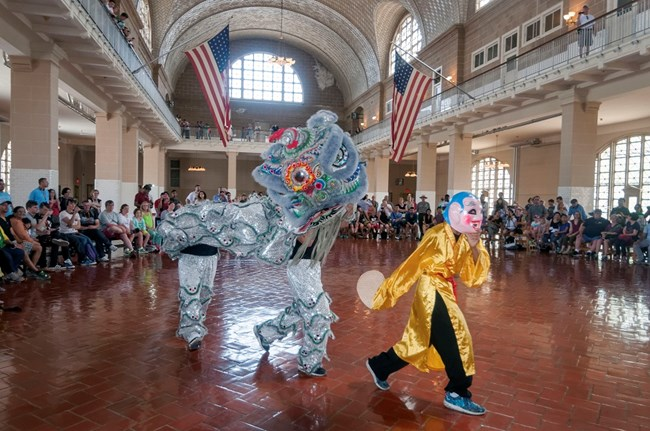 Ellis Island Asian Pacific Heritage event, performers are in costume with a crowd of visitors watching
