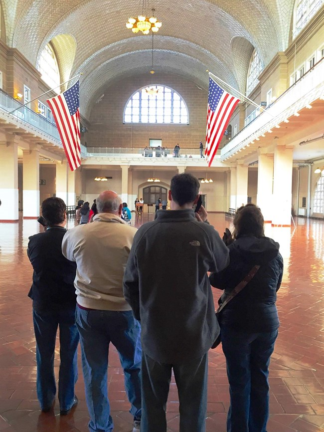 Visitors with an audio tour in the Great Hall on Ellis Island