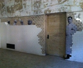 Nurses and doctors seem to appear from behind a tile wall as part of the JR exhibition in the Ellis Island Hospital complex.