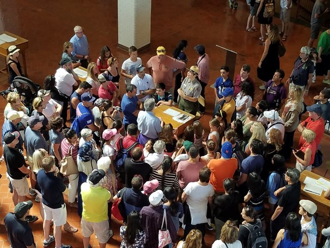 Many visitors gather around a ranger tour in Great Hall of Ellis Island.