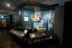 View of the Sicurella Family case located in the Treasures from Home exhibit gallery.