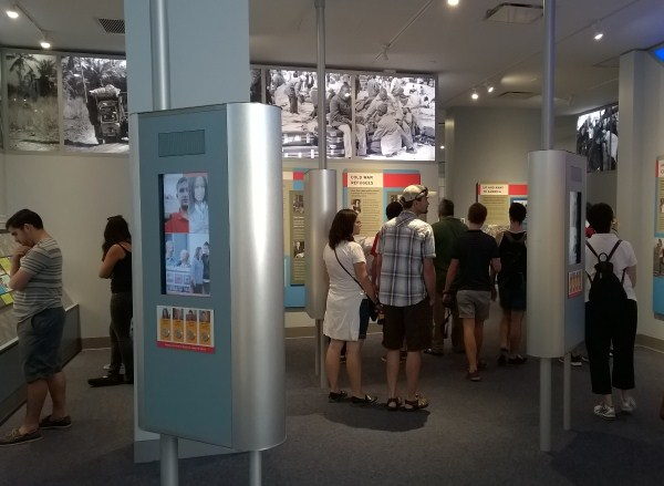Visitors in New Eras Gallery looking at exhibit text, watching video, and listening to audio.