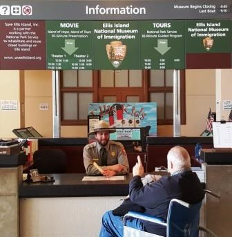 Information desk with ranger and visitor in wheelchair.