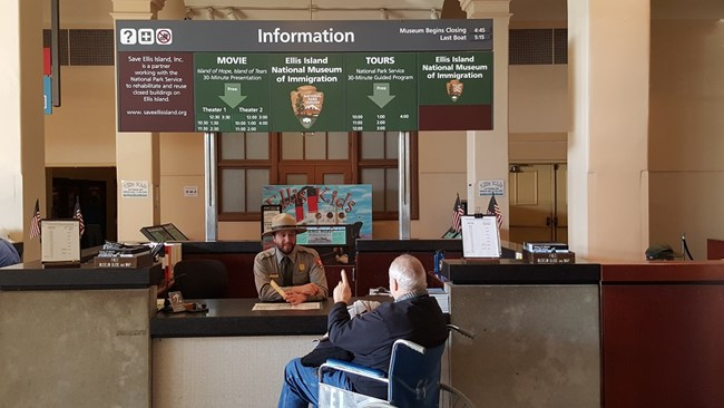 A visitor with a park ranger at the Ellis Island Information Desk