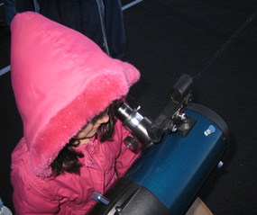 A young girl explores the rings of Saturn with a telescope.
