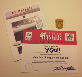 The Junior Ranger badge, book, and certificate from El Malpais National Monument.
