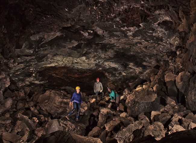 Three cavers stand on a floor of boulders beneath a craggy lava tube ceiling.