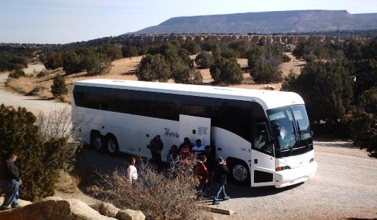 A tour bus unloads visitors at Sandstone Bluffs