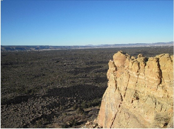 A view at Sandstone Bluffs with sandstone in the front and lava in the background.