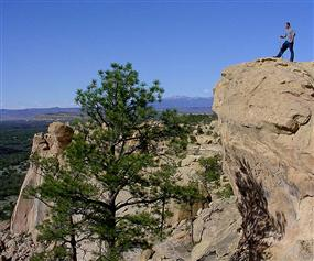 A hiker enjoys the view from the Sandstone Bluffs Overlook