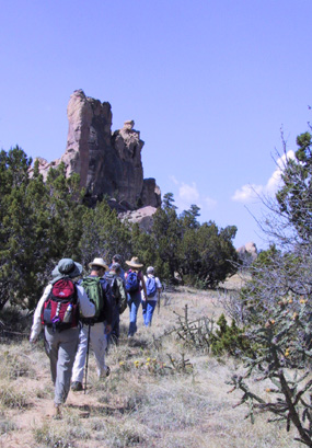 Hikers trek past sandstone buttes in El Malpais.