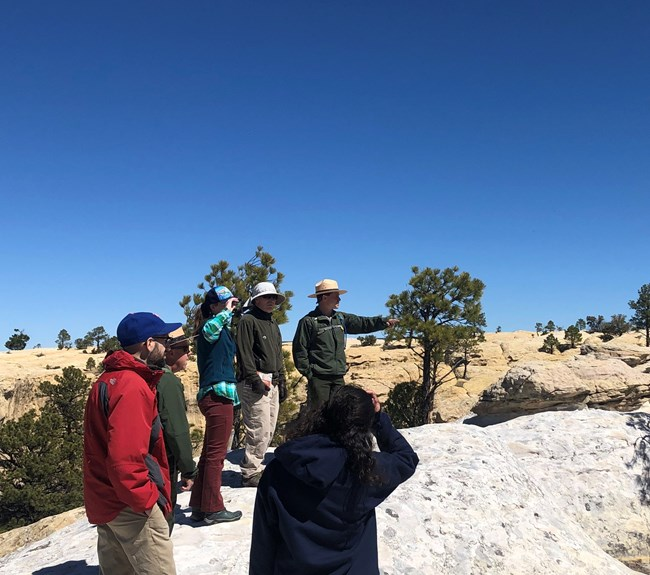 Ranger speaks with a group of visitors on the white sandstone atop El Morro with blue skies in the background.