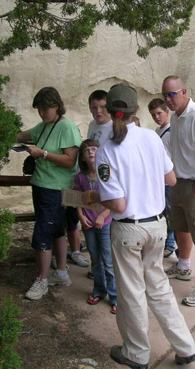 Image of a volunteer talking with visitors on the trail