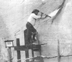 Image of the first superintendent chiseling a groove in the rock to reroute water flows around an old Spanish inscription