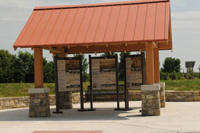 three upright wayside exhibits with a stone base and roof shelter structure over them. CCSP funded an outdoor kiosk shelter with wayside exhibits about the Santa Fe, Oregon, and California National Historic Trails in Gardner, Kansas.