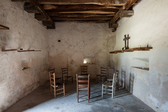 inside of a ranch building with ceiling vigas, 8 chairs, and a cross