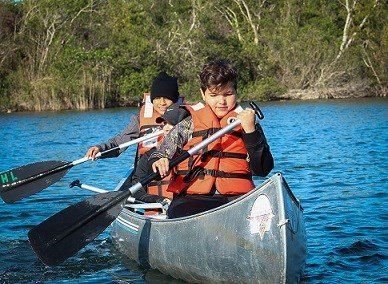 two boys in a canoe rowing