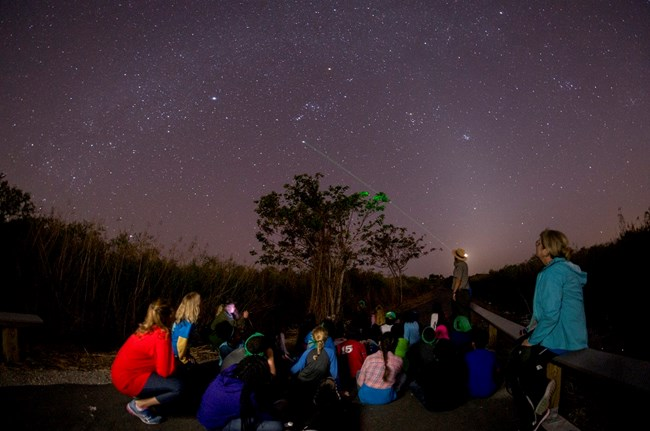 Children sitting on paved trail at night. Park ranger points laser to the sky filled with stars.