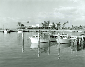 Distant view of the Flamingo Visitor Center in back of docks with small boats tied up, 1964