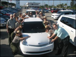a photo that shows several park employees hugging their new hybrid car