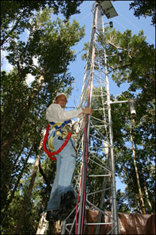 photo of a park scientist and an almost 90 ft tower that monitors the interactions of carbon in a mangrove community
