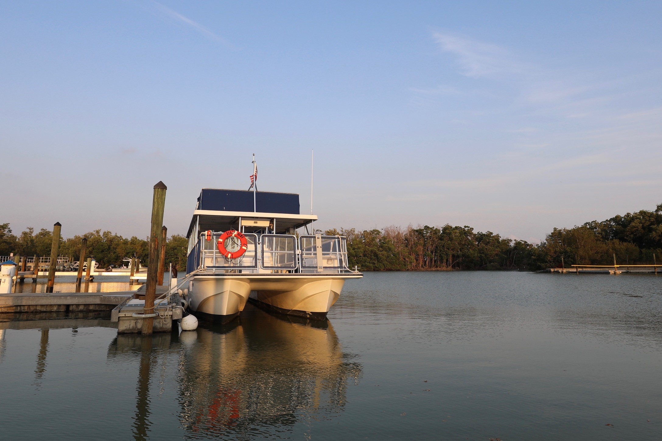 A tour boat docked at the Flamingo Marina in Everglades National Park. The sky is blue and mostly clear and there are mangrove trees in the background.