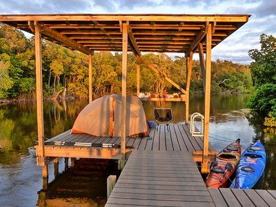 A tent on a lifted, wooden platform that sits above water. 2 kayaks are tied to the side, next to trees.