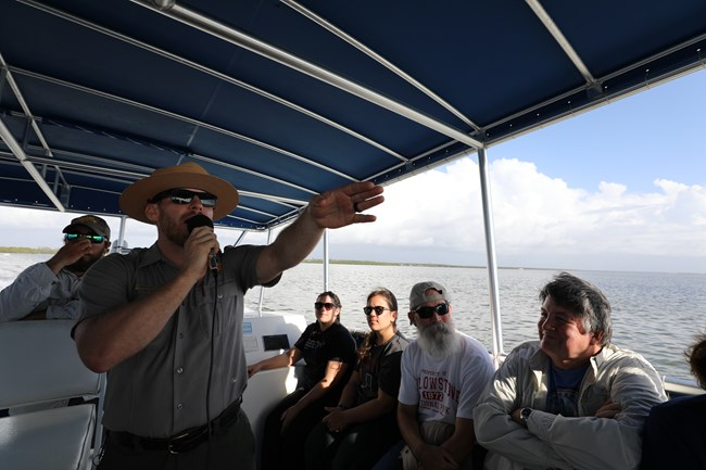 A male Park Ranger wearing sunglasses and flat hat holds a microphone in one hand and points with the other. He is aboard a boat and there are four visitors watching him.