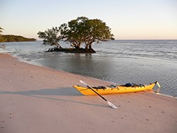 A kayak lies on top of the sand