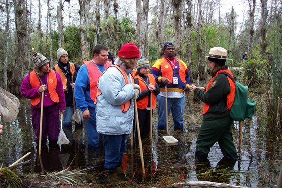 Ranger and visitors on a wet hike in a Cypress Dome