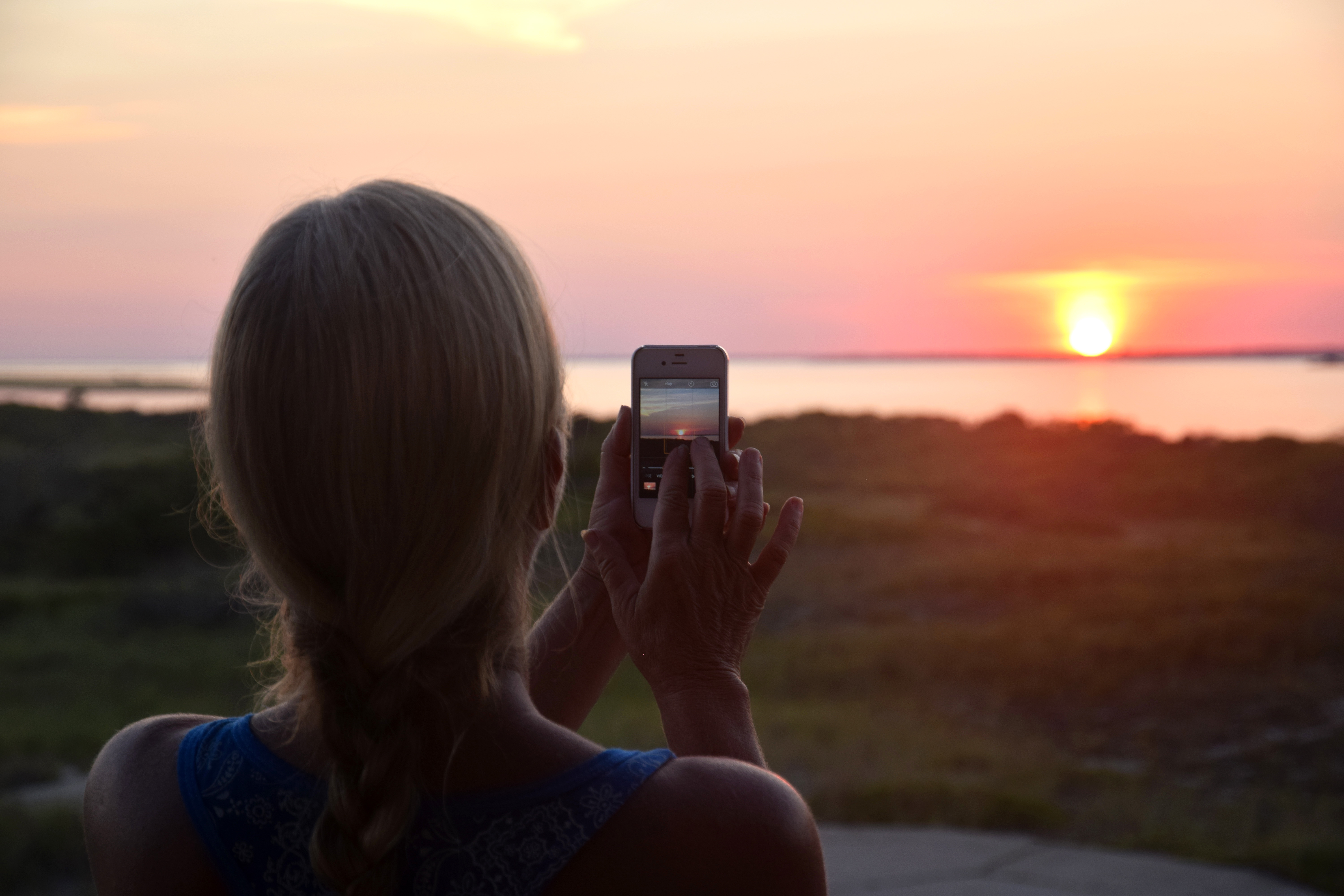 A woman uses a cell phone to photograph sunset.
