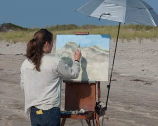 An artist with long hair stands on the beach painting a watercolor picture of grassy dunes.