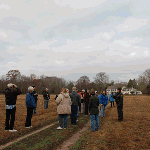 Ranger with group in field in front of historic house during fall tour.