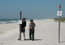 Ranger and volunteer install signs and fencing on beach.