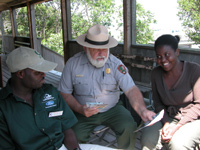 Park ranger shows brochures to two students.