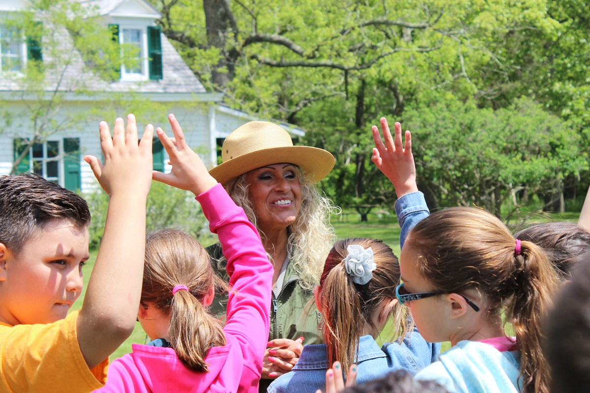 A group of students raise their hands in front of female park ranger.