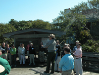 Park ranger talks to group of adults on platform in front of visitor center.