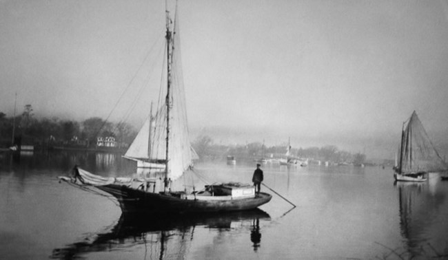 A black and white image of a Gil Smith boat floats on the Patchogue River.
