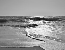 A black and white image of waves crashing on shore.