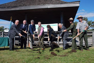 Groundbreaking participants sling their shovels of dirt in front of the old ferry terminal building.