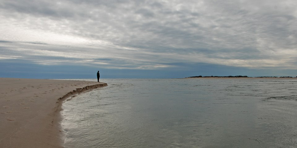 A person stands at the edge of the breach shoreline.