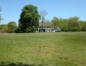 Expanse of green lawn in front of the William Floyd Estate manor house, flanked by tall leafy trees.