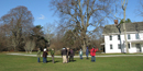 Group gathers in front of white manor house surrounded by large trees.