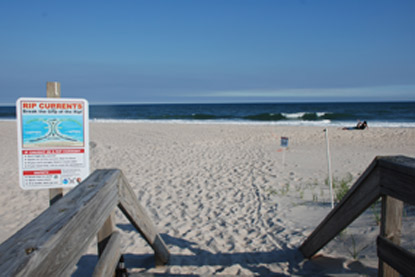 Sign along boardwalk to beach warns of rip current hazards.