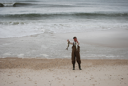 Fisherman with bluefish in surf.