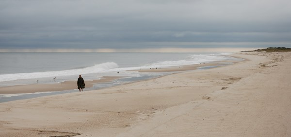 Lone hiker strolls along beach, as rain falls from thick dark clouds on the horizon.